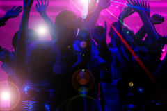 People dancing in club with laser. Silhouettes of dancing people having a celebration in a disco club, the light show is sending laser beams through the backlit Royalty Free Stock Photography