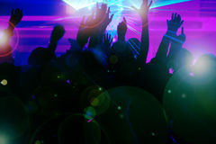 People dancing in club with laser. Silhouettes of dancing people having a celebration in a disco club, the light show is sending laser beams through the backlit Stock Image