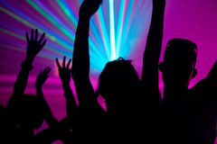 People dancing in club with laser. Silhouettes of dancing people having a celebration in a disco club, the light show is sending laser beams through the backlit Royalty Free Stock Photo