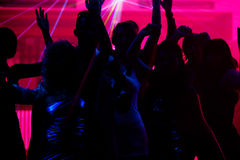 People dancing in club with laser. Silhouettes of dancing people having a celebration in a disco club, the light show is sending laser beams through the backlit Royalty Free Stock Photos