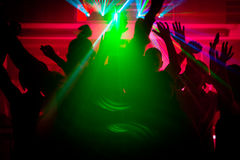 People dancing in club with lightshow stock image