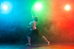 People, dancing and jazz funk concept - European young woman demonstrates flexibility over colored background. People and dancing concept - European young woman royalty free stock photography