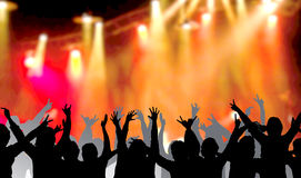 People dancing at concert. Black silhouette of people dancing with hands above hair under bright concert lights Stock Photos