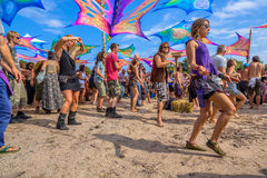 People dancing during daytime at Psy-Fi. LEEUWARDEN, NETHERLANDS-AUGUST 30, 2015: Colorful party people dancing on the sandy dancefloor during daytime on Psy-Fi Royalty Free Stock Images