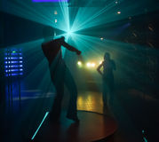 People dancing in disco lightshow Royalty Free Stock Images