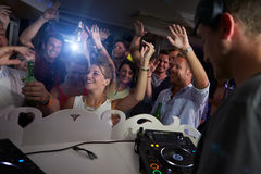 People Dancing In Nightclub With DJ In Foreground Stock Photography