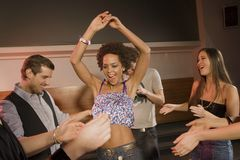People dancing at a nightclub. People dancing at a nightclub, women in centre with arms above her head Stock Images