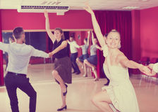 People dancing rock-and-roll. Young positive people dancing rock-and-roll in pairs Stock Images