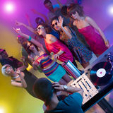 People dancing and shouting at party. Dj mixing music at party in front of young attractive caucasian people shouting and dancing wth their hands up in the air Stock Photos