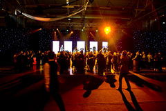People dancing at stage. A dim view of a crowd of people dancing near a stage at a nightclub or concert royalty free stock photos