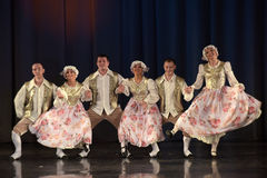 People dancing in traditional costumes on stage, Stock Image