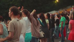 People dancing on tribune at summer live concert. Evening. Waving hands. Crowd. Adults, youth. Holidays stock video
