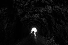 People are in a dark tunnel in the rock silhouettes on a light b Stock Image