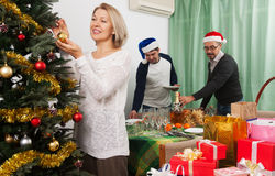 People decorate Christmas tree Stock Images