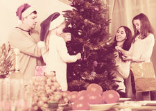 People decorating Christmas tree Royalty Free Stock Photo