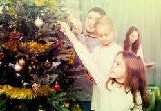 People decorating Christmas tree Stock Photo