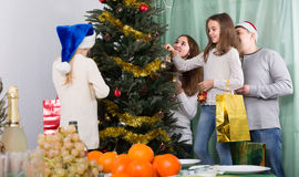 People decorating Christmas tree Stock Image