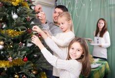 People decorating Christmas tree Royalty Free Stock Photos