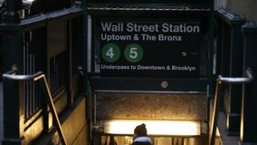 People descend to enter the Wall Street Subway Station in New York City