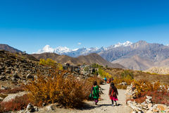 People descending down a dirt path to Muktinath. Sacred place for Hindus and Buddhists Royalty Free Stock Photography