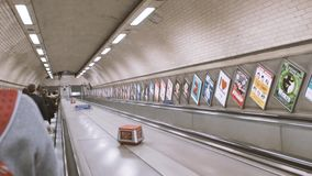 People descending escalator in London metro tube station. London, United Kingdom - circa 2018: Commuter passenger POV a the Stand on the right sign and stock video