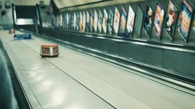 People descending escalator in London metro tube station. London, United Kingdom - circa 2018: Commuter passenger POV a the Stop Push emergency button and stock video footage