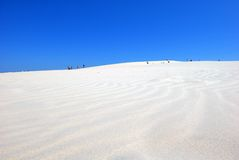 People on the desert. People walking on the white sand dunes in the desert on the blue sky backround Royalty Free Stock Photo
