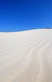 People on the desert. People walking on the white sand dunes in the desert on the blue sky backround Stock Image