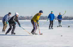 People of different ages playing hockey on a frozen river Dnepr in Ukraine. Dnepr, Ukraine - January 22, 2017: People of different ages playing hockey on a stock photography