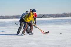 People of different ages playing hockey on a frozen river Dnepr in Ukraine. Dnepr, Ukraine - January 22, 2017: People of different ages playing hockey on a royalty free stock photography
