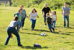 People of different ages taking photos on the lawn. Happy cheerful positive smiling people of different ages playing football on grass stock images