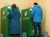 People of different generations use the services of ATMs of Sberbank Royalty Free Stock Photo