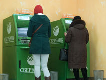 People of different generations use the services of ATMs of Sberbank Stock Image