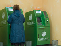 People of different generations use the services of ATMs of Sberbank Stock Photos