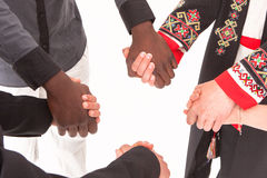People of different nationalities and religions hold hands. The concept of friendship among peoples. Business concept of team building and partnerships stock photography