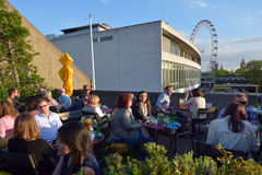 People dining outside the Royal Festival Hall in with London Eye. LONDON, UK - MAY 15 2015:People dining outside the Royal Festival Hall in with London Eye in royalty free stock images