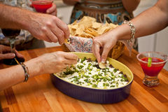 People dipping chips. People dipping into bowl of chip dip, studio shot Royalty Free Stock Photo
