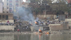 People at dirty ghat, with fire burning on shore, view from a boat. stock video