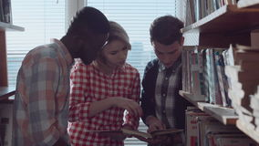 People discussing books between stacks stock video
