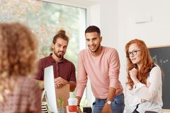 People discussing with team leader. Creative young people discussing a new project with team leader during business meeting in the office Royalty Free Stock Photos