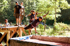 People Dive Into Blood Pit On Zombie Obstacle Course Race. Dalton, GA, USA - September 14, 2013: Two people jump into the blood pit, one of the many obstacles royalty free stock photo