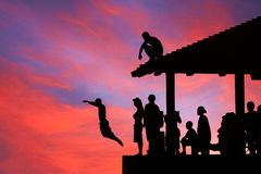People diving in magical sunset, Hawaii Stock Photo