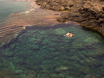 People diving in a natural basin in the rocks coastline of Lanzarote. Snorkling in crystal clear water in a natural basin in Lanzarote, Spain at the coast stock photography