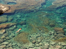 People diving in a natural basin. In the rocks coastline of Lanzarote royalty free stock image