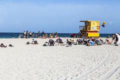 People do fitness training at the beach next to a lifeguard tower Royalty Free Stock Image