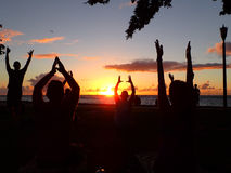 People do sunset yoga for charity on Waikiki Beach with plane in Stock Photography