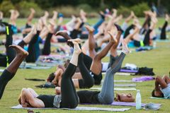 People Do Yoga Pose Lying Down In Group Yoga Class. Atlanta, GA, USA - July 2, 2017:  Dozens of people do a yoga pose lying on their backs as they take part in a Royalty Free Stock Image