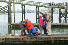 People on dock looking at crab pot. Westport, WA, USA August 21, 2016: Group of children look at crabs in pot while two adults watch over them Royalty Free Stock Image