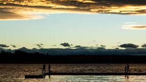 People on a dock silhouetted in the sunset Stock Photography