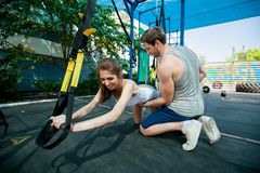 people does suspension training with fitness straps outdoors Stock Photos